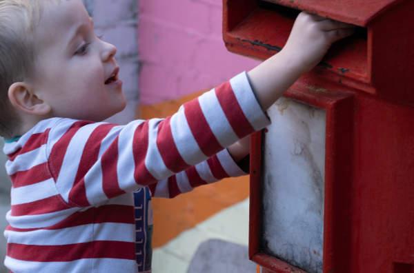 Child making a donation into the farmyard post box