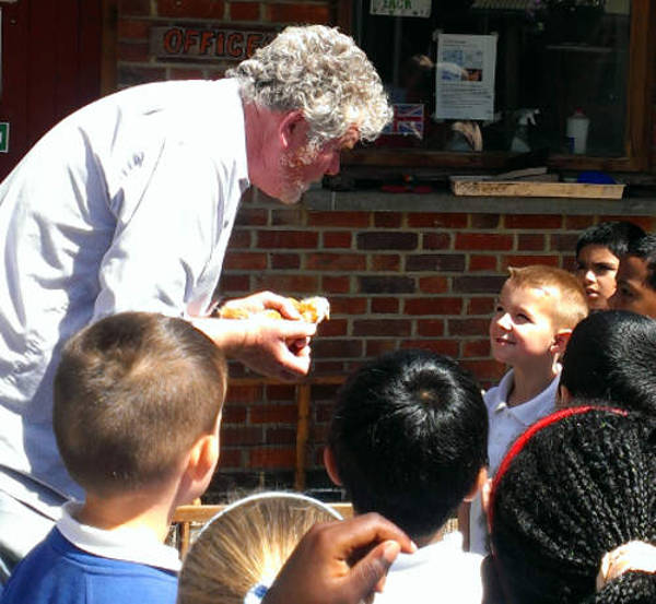Farm Education Officer shows school children a baby chick