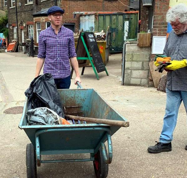 Corporate volunteer using  wheelbarrow for task
