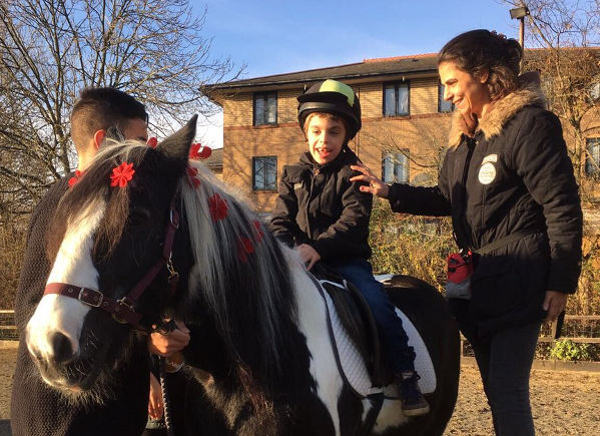 Riding therapy session for a child, with two assistants