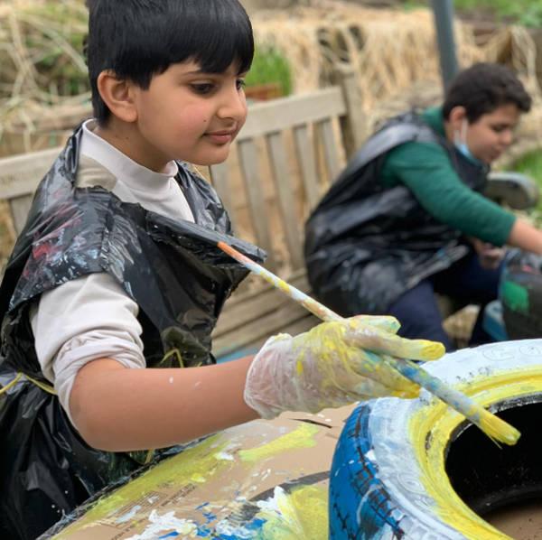 Playscheme children painting tyres in garden