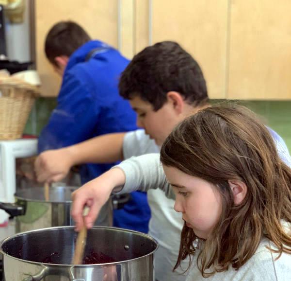 Children stirring jam in big pans