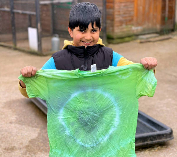 Child shows tie-dyed t-shirt